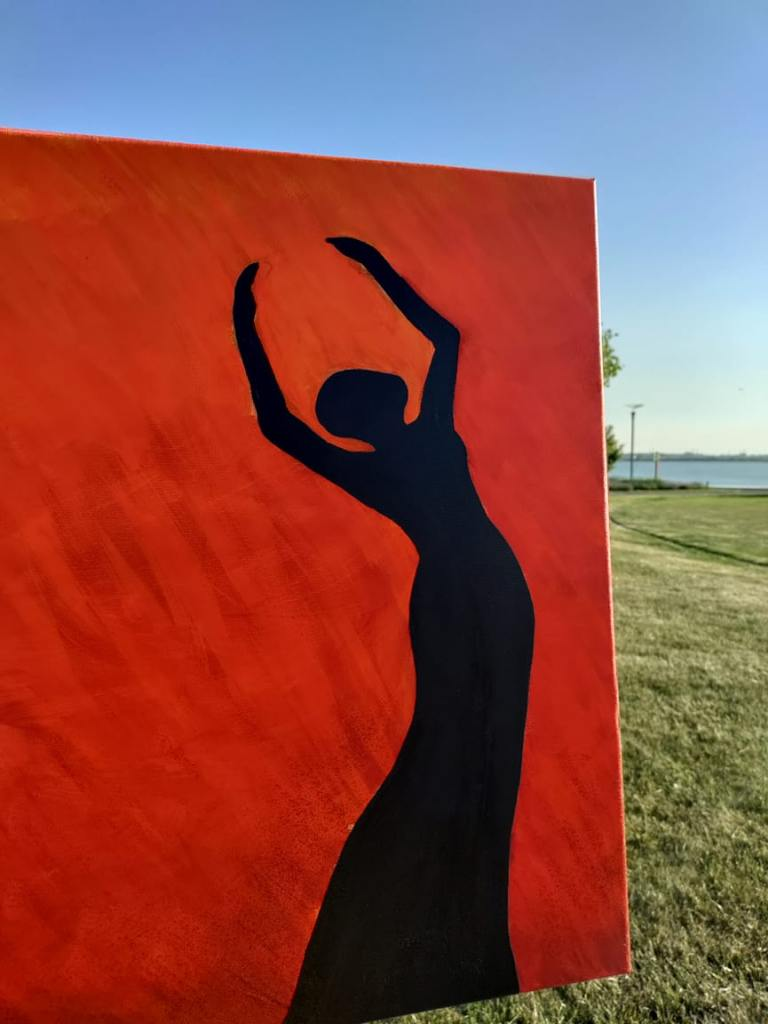 Pictured: A painting. Red orange flames cover canvas background. All black silhouette of a praise dancer with arms fully extend in worship, back arched. Caption: My newest painting in my Sunsets & Silhouettes Collection. Fire Dancer, by Marlene Dillon Copyright 2021.